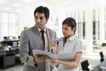 Young business people looking away while holding document