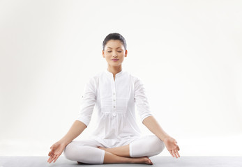 Young woman meditating over white background