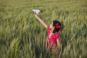 Little girl playing with paper plane in the field