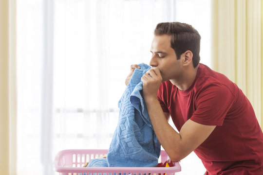 Young man smelling clean towels in laundry