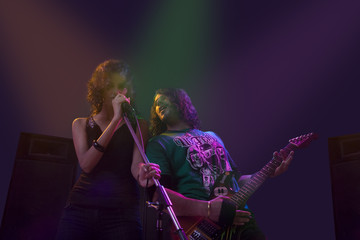 Woman singing while man plays on the guitar