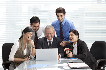 Smiling colleagues at table with laptop