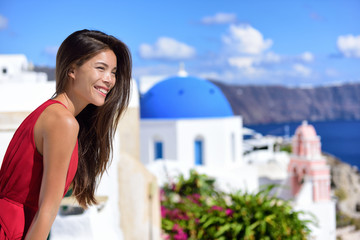Fototapete - Europe travel cruise destination Santorini woman at Oia tourist landmark attraction, the blue domed church. Happy Asian girl smiling relaxing in summer sun on cruise holiday.