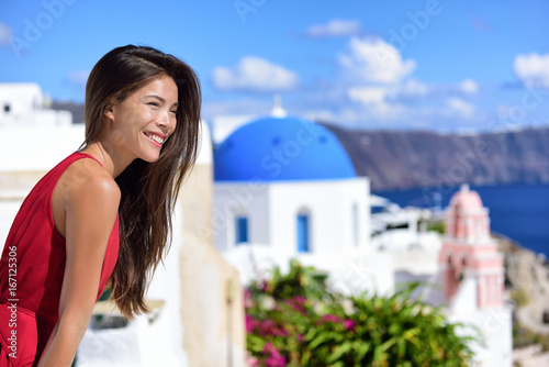 Wall mural Europe travel cruise destination Santorini woman at Oia tourist landmark attraction, the blue domed church. Happy Asian girl smiling relaxing in summer sun on cruise holiday.