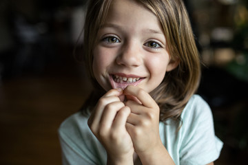 Portrait of happy girl showing tooth gap at home