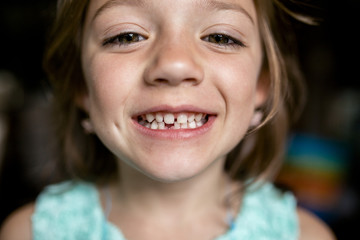 Close-up portrait of girl showing gap tooth