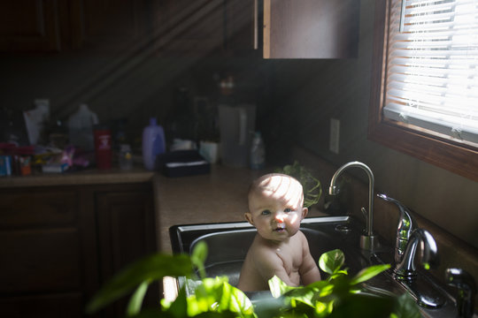 Portrait of baby girl playing in kitchen sink at home