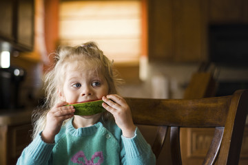 Girl looking away while eating watermelon slice at home