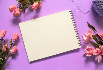 Romantic roses flat lay with blank page notebook on violet background.