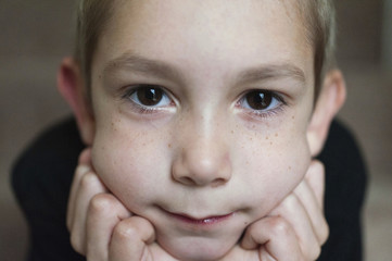 Close-up portrait of boy with hands on chin at home