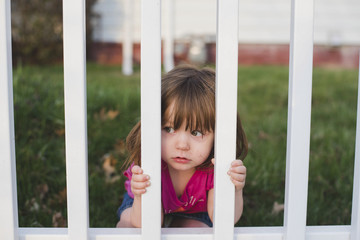 Cute girl looking through fence in backyard
