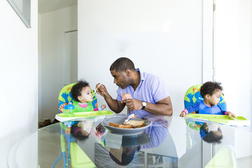 Father feeding baby girl while sitting by daughter at table