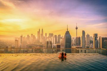 Fotobehang Kuala Lumpur Traveler couple woman in swimming pool on the roof top of hotel at sunrise in Kuala Lumpur, Malaysia.