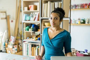 Portrait of confident businesswoman standing against racks in office
