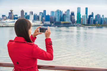 Wall Mural - Cruise tourist woman taking pictures with mobile phone of Vancouver city leaving on Alaska cruise travel. British Columbia, Canada.