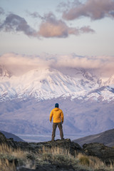 Rear view of hiker watching snowcapped mountains