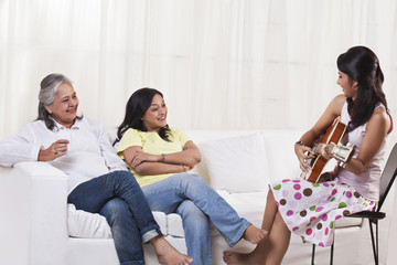 Beautiful teenage girl playing guitar for her mother and grandmother