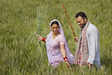 Happy Indian couple gliding through wheat field