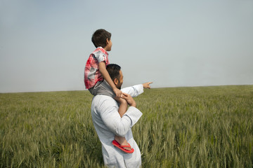 Indian man pointing at something while carrying son on shoulders
