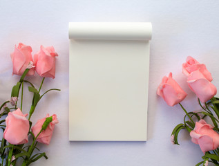 Flat lay with notepad and roses on white background. Romantic banner template with text place.