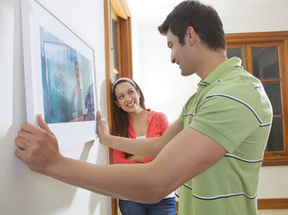 Young man hanging a picture on the wall while young woman looks