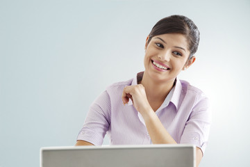 Smiling businesswoman using laptop over colored background