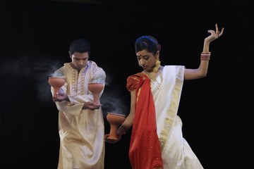Bengali couple doing a Dhunuchi dance