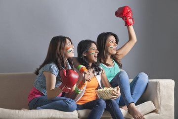 Exhilarated young women watching boxing match together at home