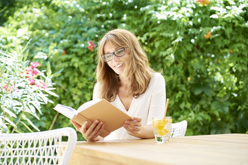 Relaxing at home. Shot of a smiling middle aged woman sitting in garden and reading a book.
