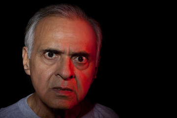 Portrait of angry senior man over black background