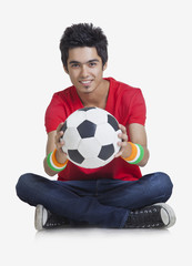 Portrait of young boy smiling while holding soccer ball over white background