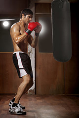 Profile shot of male boxer working out with black punching bag at gym