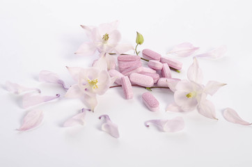 Alternative medicine tablets with flowers and petals on table