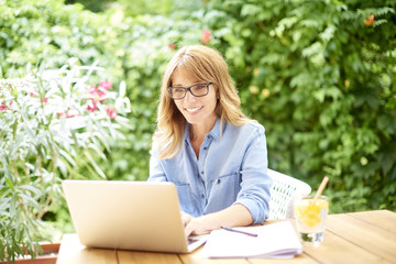 Home office. Beautiful smiling woman using her laptop while sitting at desk outdoor at home.