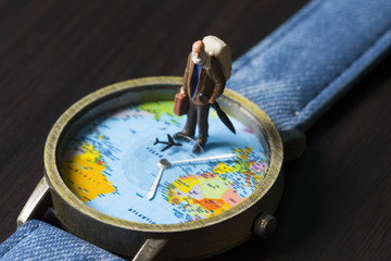 Old man on watches with world map. World travel photo banner. Senior traveler figurine.