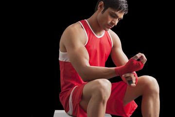 An Indian male boxer taping up hands against black background
