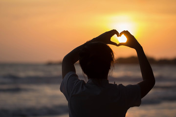 beautiful woman Heart-shaped handmade During sunset style Silhouette
