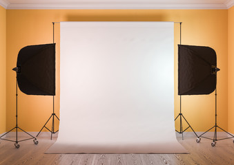 Interior of studio room with equipment. Moderate yellow color of the walls. Artificial lighting with softboxes.