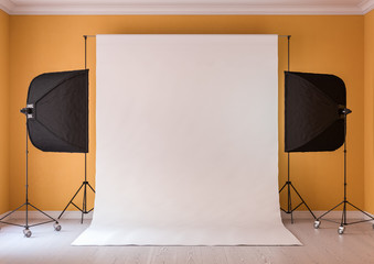 Interior of studio room with equipment. Moderate yellow color of the walls. Lighting from the window.
