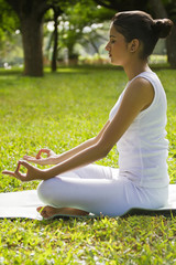 Young woman in lotus position meditating in a park