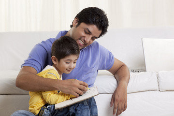 Happy father helping his son in drawing at home