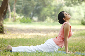 Woman doing yoga in lawn