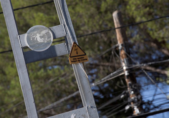 """Warning signs reading """"High voltage. Danger of death"""" (L) and """"Don't touch. Danger of death"""" are attached to a high-voltage pylon in Alpedrete"""