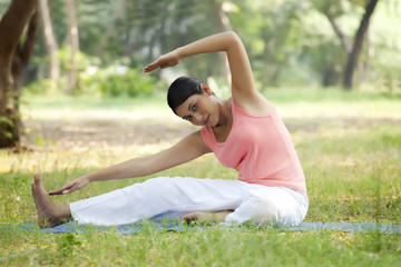 Smiling young woman doing stretching exercise