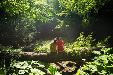 Girl and boy, couple in a wild forest surrounding. Magical fairy place.