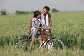 Father guiding son to ride cycle in the field