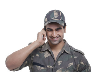 Smiling young soldier having conversation on mobile phone over white background