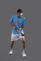 An Indian sportsman practicing hockey isolated over gray background