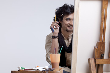 Portrait of smiling young artist with paintbrush