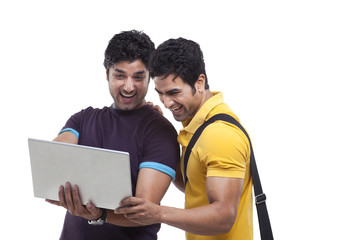 Male friends laughing while using laptop
